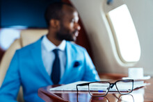 Businessman With Eyeglasses And Newspaper On Table In Private Jet