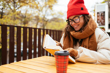 Woman Smiling While Reading Book Sitting At Sidewalk Cafe