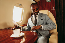 Businessman Holding Newspaper While Checking Time On Wristwatch In Airplane