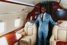 Smiling Businessman Gesturing While Standing Amidst Seats In Private Jet