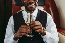 Smiling Businessman Holding Champagne In Private Jet