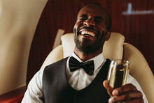 Young Male Entrepreneur Laughing While Holding Champagne In Private Jet