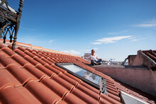 Happy Young Woman Sitting On Red Tiled Roof.