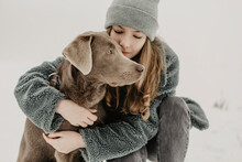 Portrait Of Teenage Girl Crouching In Snow And Embracing Labrador Retriever
