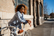 Afro Woman In Sunglasses Leaning On Bicycle Against Building
