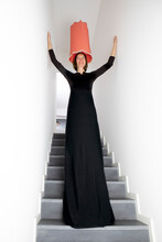 Smiling Woman In Black Dress With Arms Raised Standing On Staircase
