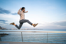Carefree Male Entrepreneur With Arms Raised Jumping By Railing In Front Of Blue Sky