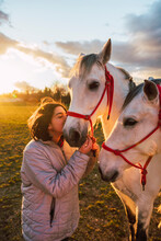Girl Wearing Jacket Kissing Horses While Standing In Ranch