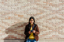 Smiling Woman With Sling Bag Holding Mobile Phone Against Brick Wall
