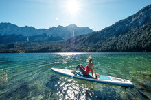 Germany, Bavaria, Garmisch Partenkirchen, Young Woman Sitting On Stand Up Paddle Board On Lake Eibsee And Looking At Zugspitze Mountain