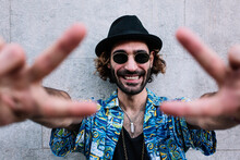 Happy Man Wearing Hawaiian Shirt Showing Peace Sign In Front Of Wall
