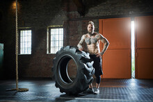 Male Athlete With Hand On Hip Standing By Tire In Sports Studio