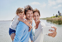Smiling Woman Taking Selfie With Family By Lake On Sunny Day