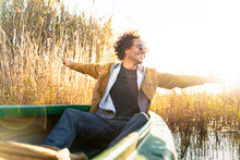 Carefree Man With Arms Outstretched Smiling While Sitting In Canoe On River