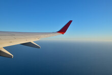 Wing Of Commercial Airplane Flying Against Clear Blue Sky