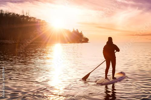 Naklejka premium Adventurous girl on a paddle board is paddeling in the Pacific West Coast Ocean. Sunset Sky Art Render. Taken near Spanish Banks, Vancouver, British Columbia, Canada.