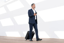 Mature Businessman With Mobile Phone Walking With Wheeled Luggage Against White Wall