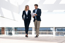 Businesswoman Having Discussion With Colleague Over Paper While Walking At Office Building Terrace