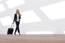 Female Entrepreneur With Mobile Phone And Luggage Walking Against White Wall
