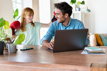 Playful Redhead Girl Having Fun With Father Working On Laptop At Home