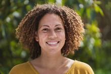 Smiling Curly Haired Woman With Freckles In Vegetable Garden