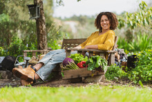 Young Smiling Woman Sitting On A Wooden Bench In Sustainable Permaculture Garden