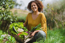 Smiling Woman Squatting While Holding Crate Of Fresh Vegetables In Garden