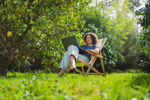 Smiling Woman Looking At Laptop While Sitting On Chair In Permaculture Garden