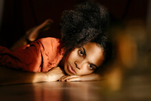 Afro Young Woman Lying On Floor At Home