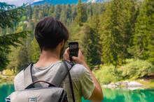 Male Hiker Taking Photo Of Cauma Lake Through Mobile Phone While Standing At Graubunden Canton, Switzerland