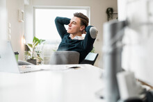 Young Male Professional Relaxing With Hands Behind Head In Home Office