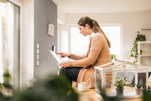 Female Professional Using Laptop Sitting On Desk At Home