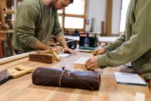 Craftsmen Working At Table In Workshop