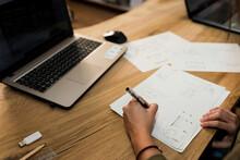 Female Carpenter Making Design On Paper At Desk In Industry