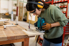 Female Carpenter Working With Router Jig At Workbench In Industry