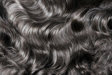 Black Hair Texture. Wavy Long Curly Dark Hair Close Up As Background. Hair Extensions, Materials And Cosmetics, Hair Care. Hairstyle, Haircut Or Dying In Salon.