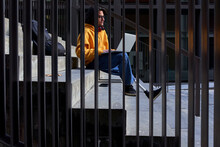 Disabled Man With Leg Prosthesis Using Laptop While Sitting On Steps Seen Through Metal Railing