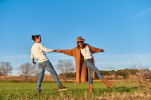 Man Pulling Girlfriend On Green Field Against Blue Sky During Sunset