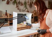 Female Entrepreneur Arranging Handmade Soaps In Box At Workshop