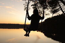 Silhouette Of A Romantic Young Woman On A Swing Over Lake At Sunset. Young Girl Traveler Sitting On The Swing In Beautiful Nature, View On The Lake