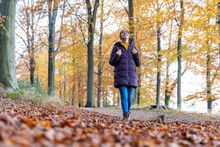 Smiling Woman Holding Backpack While Looking Up In Autumn Forest