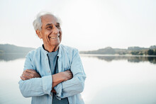 Happy Man Looking Away While Standing With Arms Crossed Against Water