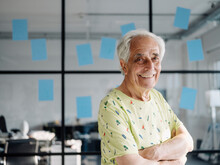 Confident Businessman With Arms Crossed Smiling While Standing Against Glass Wall