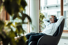 Relaxed Businessman With Hands Behind Head Listening Music Through Headphones While Sitting On Massage Chair In Office Corridor