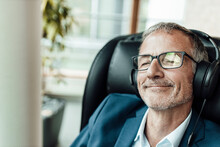 Smiling Businessman With Eyeglasses Listening Music Through Headphones While Sitting On Chair In Office Corridor