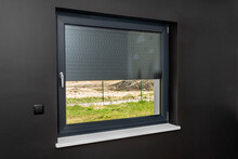 A Large Window In A Room With Black Walls, Half Covered With External Blinds.