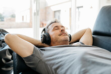 Mature Man Listening Music Through Headphones While Relaxing On Sofa In Living Room
