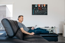 Mature Man With Digital Tablet Looking Away While Sitting On Sofa At Home