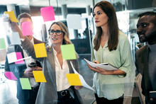 Businesswoman Discussing Over Adhesive Note On Glass Wall While Standing With Colleague In Office