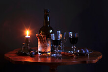 Studio Shot Of Bottle Of Red Wine, Three Filled Wineglasses, Plums, Salty Pretzels And Burning Candle On Small Coffee Table